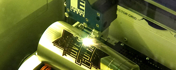Metal cannister being engraved with an Epilog fiber laser machine